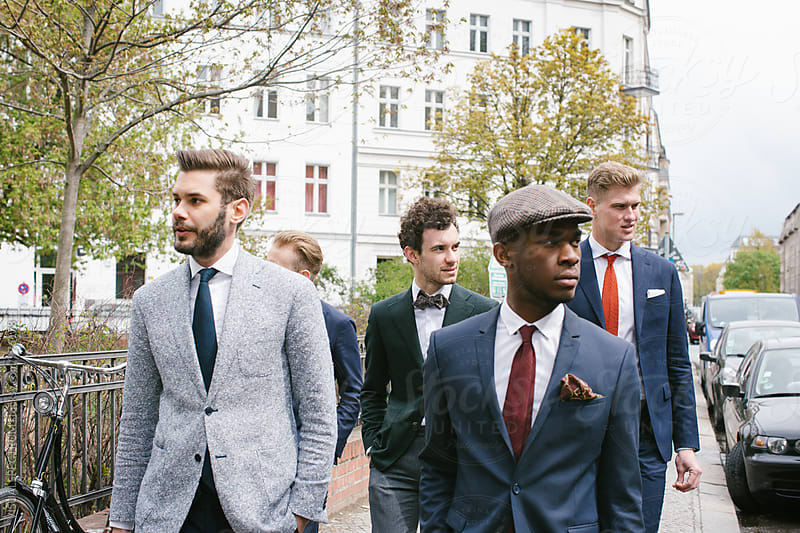 Group of Four Stylish Young Men in Suits Walking Down Street by VISUALSPECTRUM for Stocksy United