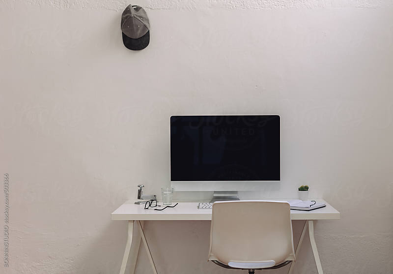 Desk computer in a white industrial office. by BONNINSTUDIO for Stocksy United