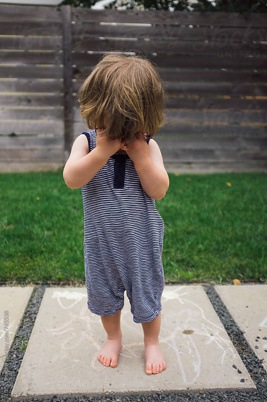 A young boy stands with his head in his hands. by Lucas Saugen for Stocksy United