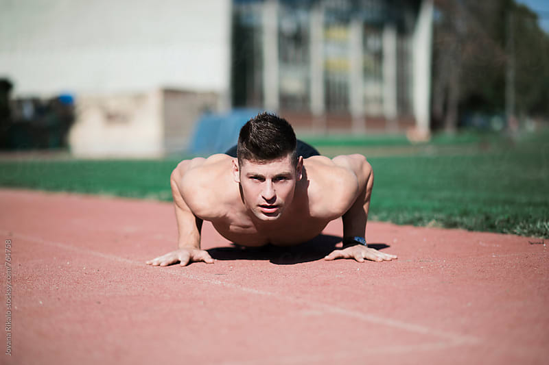 Man doing pushups outdoors by Jovana Rikalo for Stocksy United