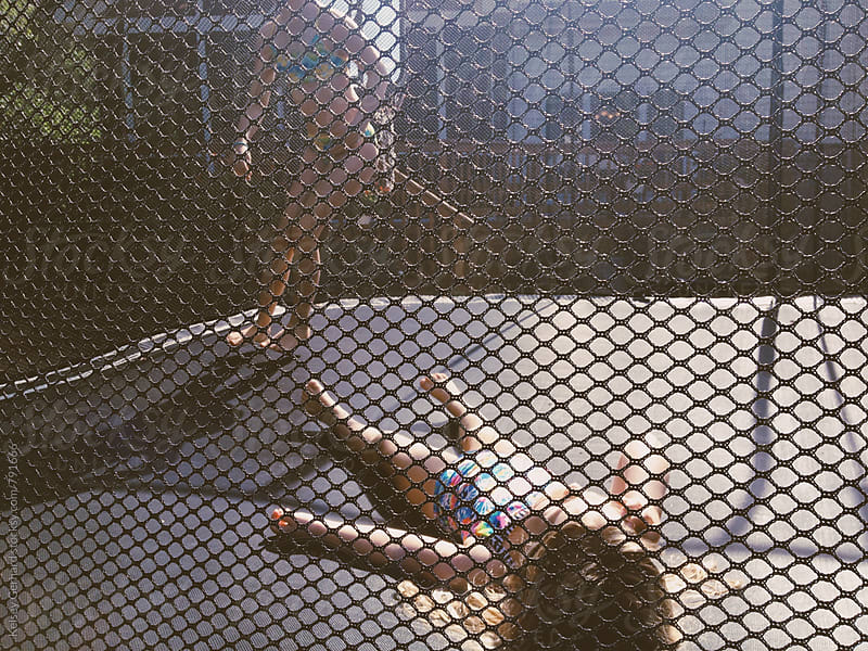 Two girls play on a trampoline. by Kelsey Gerhard for Stocksy United