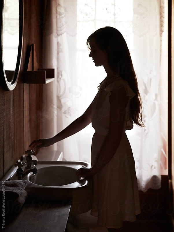 Silhouetted woman using sink in bathroom by Trinette Reed for Stocksy United