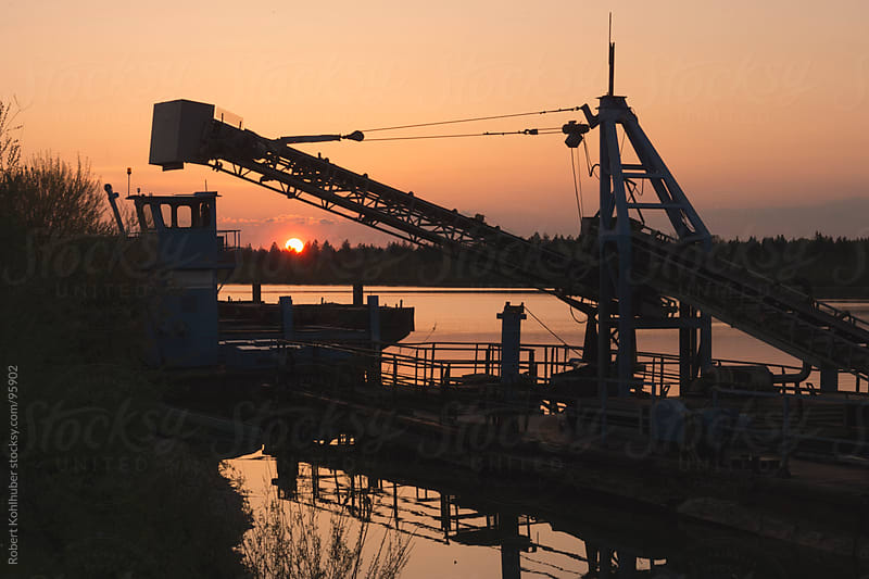 Abandoned industry machines at sunset over lake by Robert Kohlhuber for Stocksy United