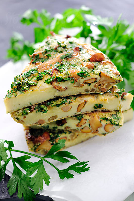 Food: Pieces of Chantarelle Frittata and Parsley by Ina Peters for Stocksy United