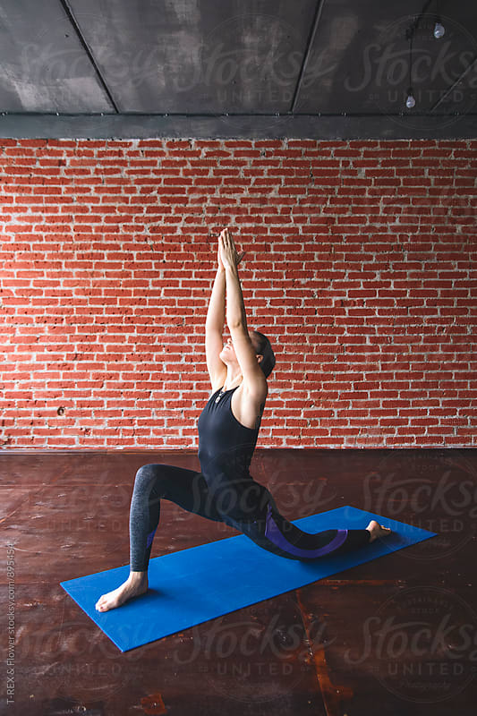Young woman performing Low Lunge yoga pose by Danil Nevsky for Stocksy United