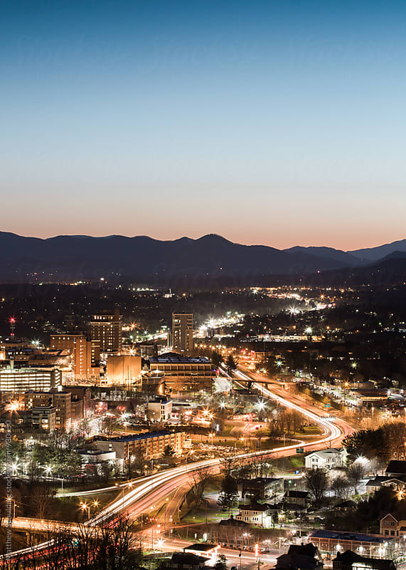 Asheville city skyline at night with traffic motion by Matthew Spaulding for Stocksy United