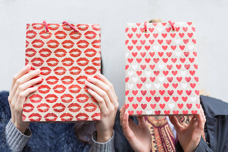 Best Friends Covering Their Faces with Shopping Bags by HEX . for Stocksy United