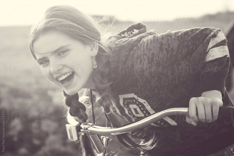 A young teen girl laughs while riding her bike.  by Tana Teel for Stocksy United