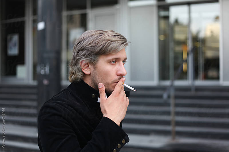 Portrait of a stylish man smoking cigarette in the street by VeaVea for Stocksy United