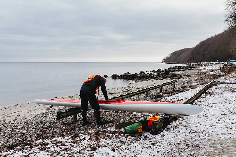 Man cleaning kayak  by Lior + Lone for Stocksy United