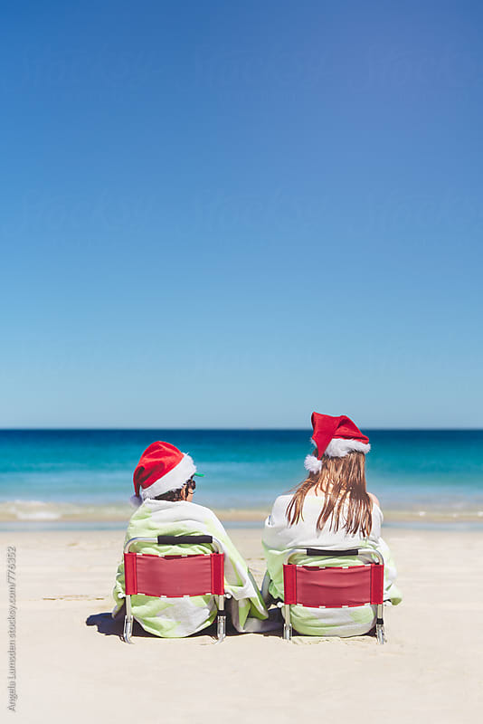 Two children sitting on red chairs at the beach on Christmas Day, viewed from behind by Angela Lumsden for Stocksy United