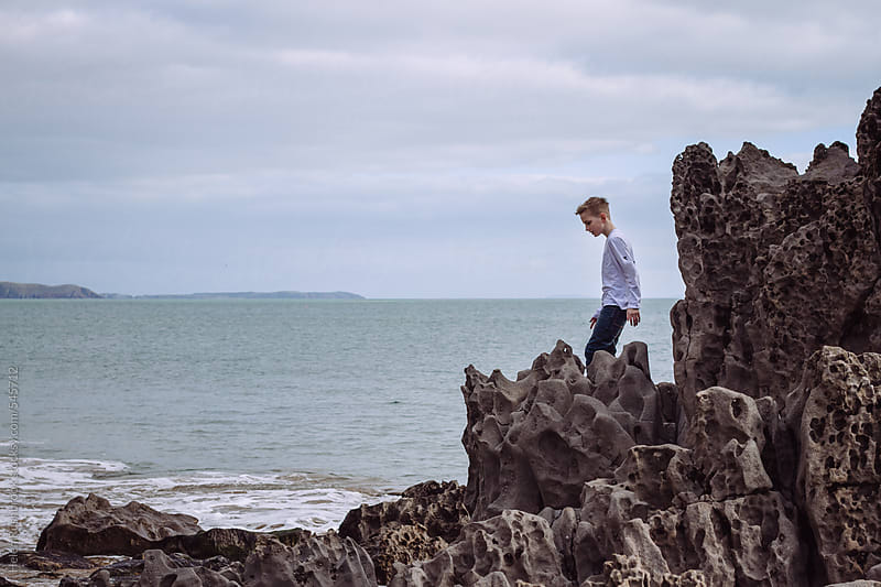 A young boy exploring a rocky shoreline by Helen Rushbrook for Stocksy United