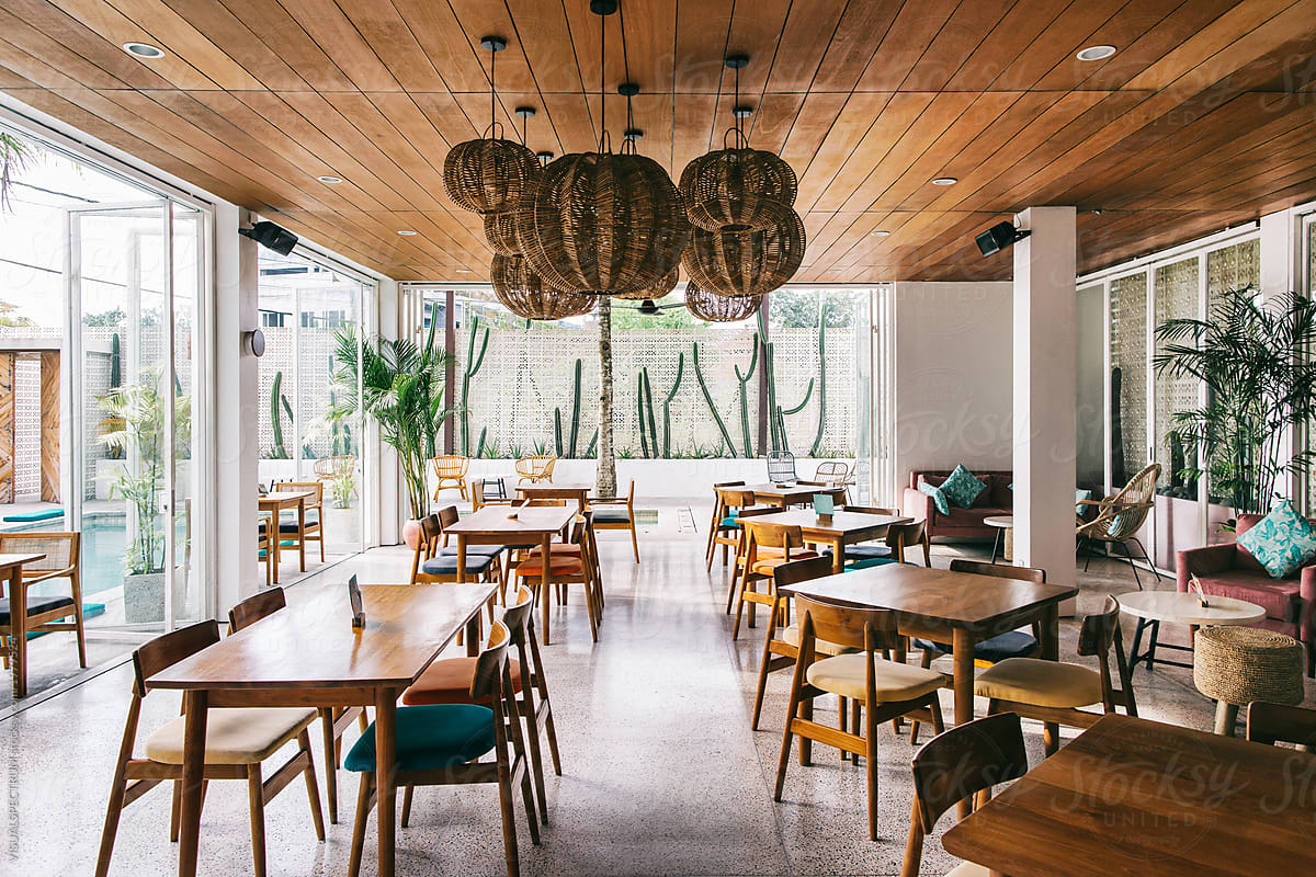 Tropical interior design restaurant tables and chairs in hip r by visualspectrum for stocksy united
