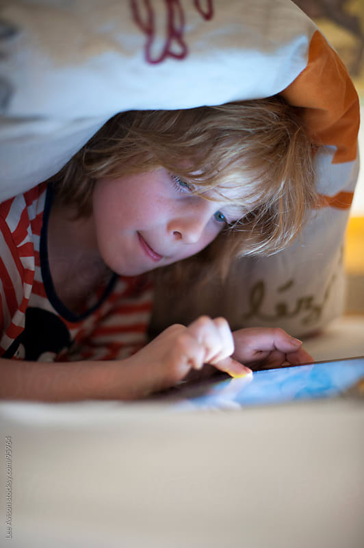boy using a digital tablet in bed by Lee Avison for Stocksy United