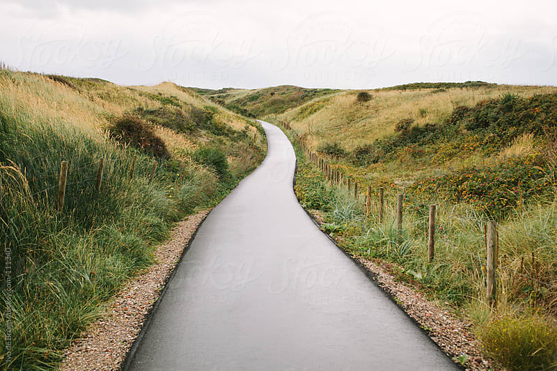 Empty path in the dunes underneath a cloudy sky by Ivo de Bruijn for Stocksy United