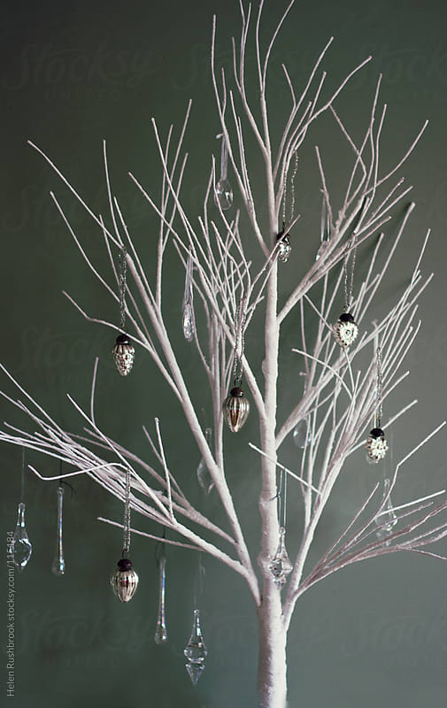 A white paper tree with crystal and silver ornaments on it. by Helen Rushbrook for Stocksy United