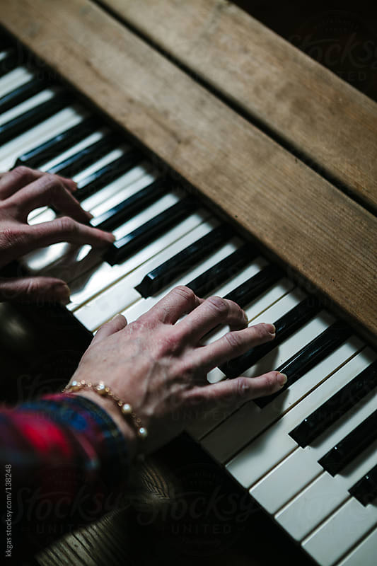 hands playing a piano. by kkgas for Stocksy United