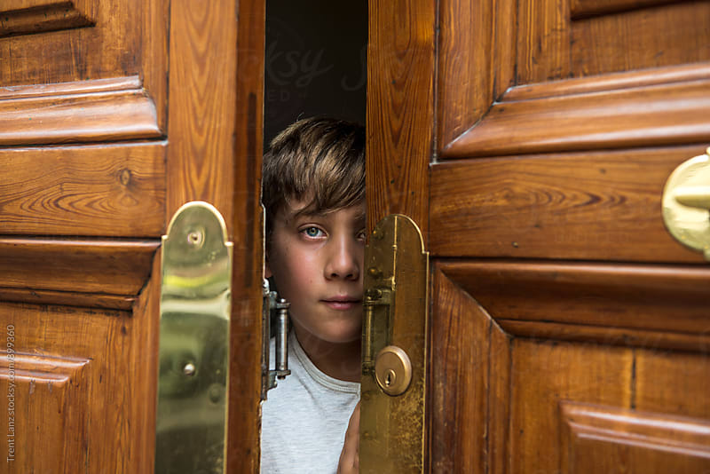 Boy peeping out from wooden door by Trent Lanz for Stocksy United