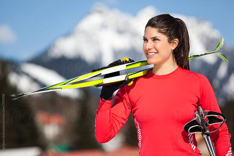 Female skier preparing to go cross-country skiing on a sunny winter day by Suprijono Suharjoto for Stocksy United