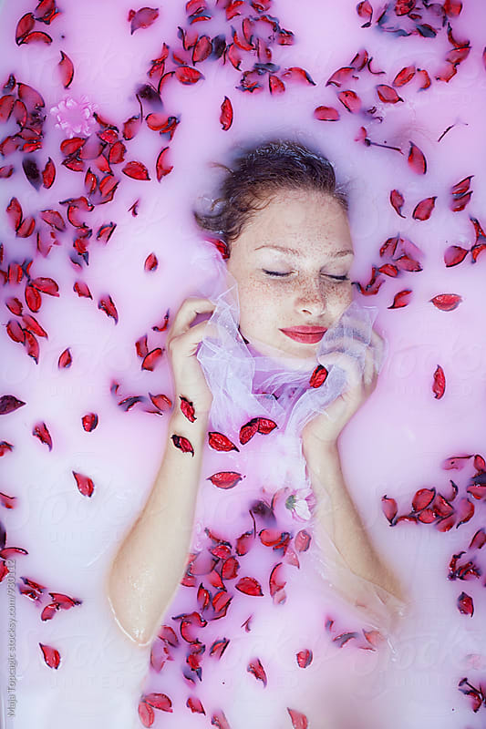 Portrait of a beautiful redhead with freckles having a milk bath by Maja Topcagic for Stocksy United