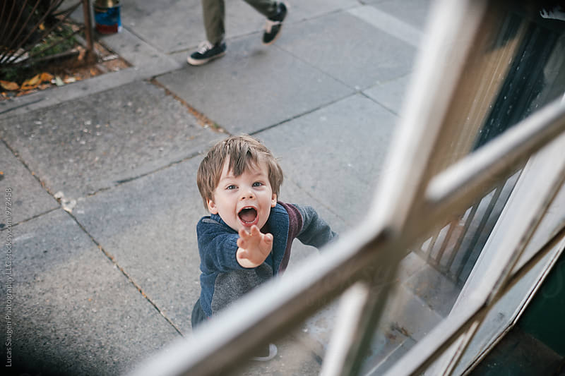Young toddler waving enthusiastically through a window. by Lucas Saugen for Stocksy United