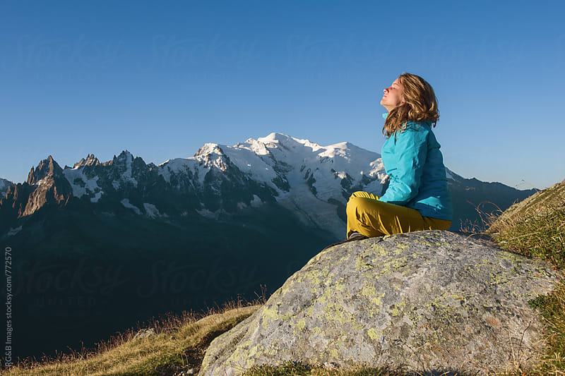 Young woman sitting on a rock with Mont Blanc behind her  by RG&B Images for Stocksy United