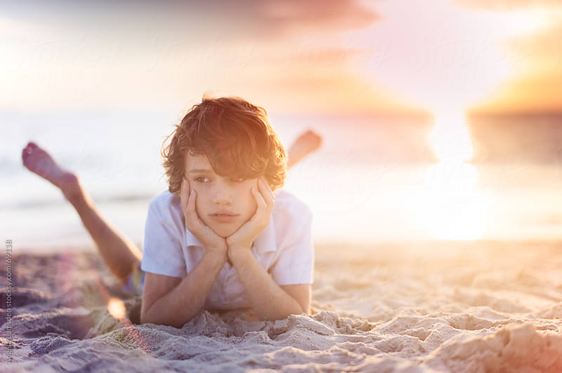 Boy relaxing at the beach at sunset by Angela Lumsden for Stocksy United