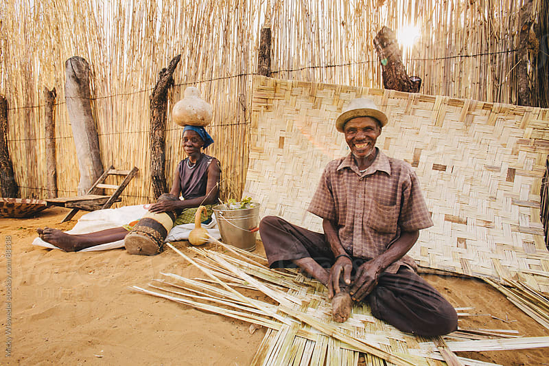 Namibian Hambukush man and woman weaving outside their kraal by Micky Wiswedel for Stocksy United
