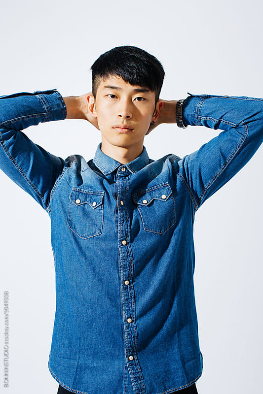 Portrait of a serious asian man wearing denim clothes over white background.  by BONNINSTUDIO for Stocksy United