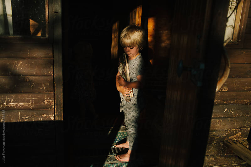 Boy carrying wood at the entrance to a wooden sauna. by Julia Forsman for Stocksy United