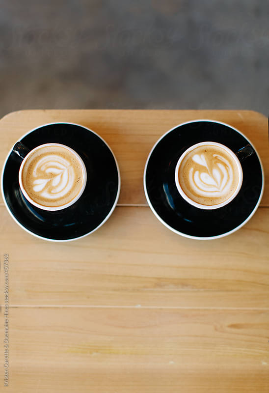 Two twin lattes on a wooden table by Kristen Curette Hines for Stocksy United