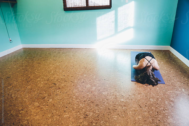 Woman in Child's Pose in Yoga Studio  by Abby Mortenson for Stocksy United
