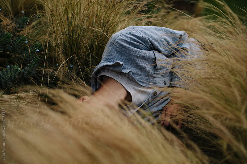 Male model in long grass. by Julia Forsman for Stocksy United