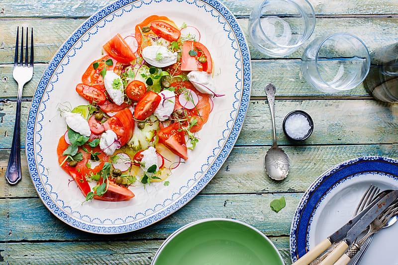 Heirloom tomato and ricotta salad on a platter. by Darren Muir for Stocksy United