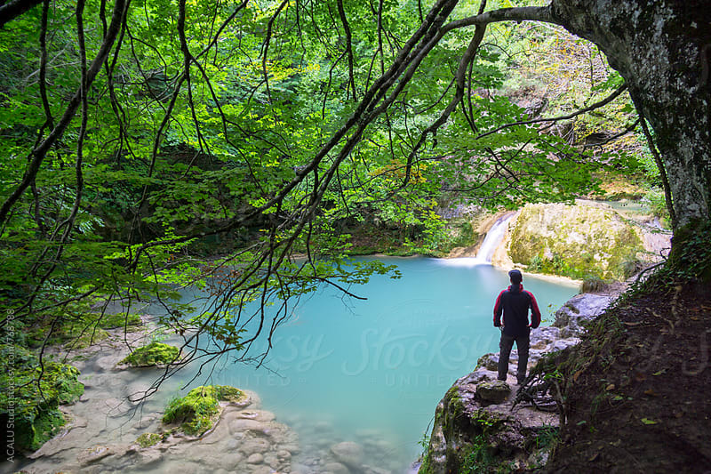 Man looking at an amazing turquoise river by ACALU Studio for Stocksy United
