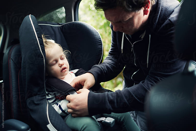Father getting child from car seat by sally anscombe for Stocksy United