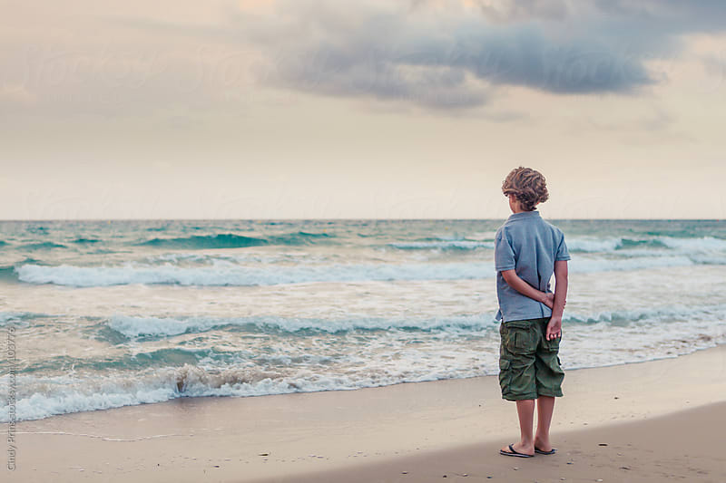 Boy standing on the beach on a cloudy summer day looking at the ocean by Cindy Prins for Stocksy United