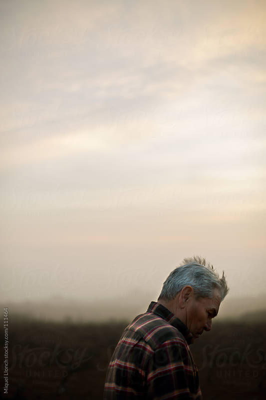 Portrait of an old farmer in the field with cloudy sky by Miquel Llonch for Stocksy United
