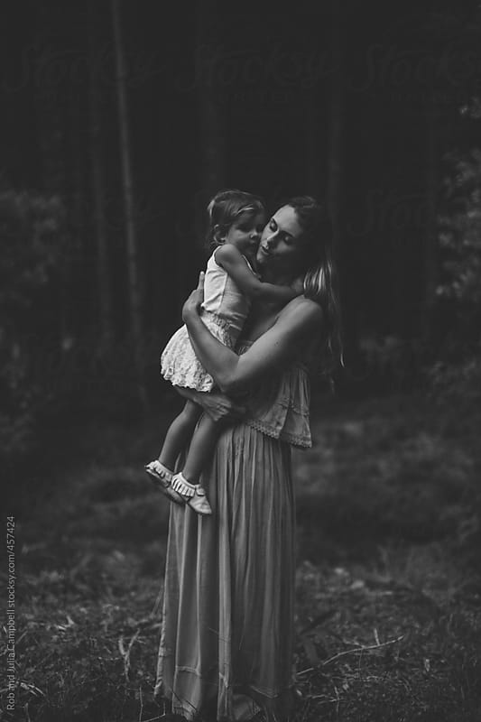 Young, stylish mom and cute toddler daugher   cuddling, hugging together in tropical forest by Rob and Julia Campbell for Stocksy United