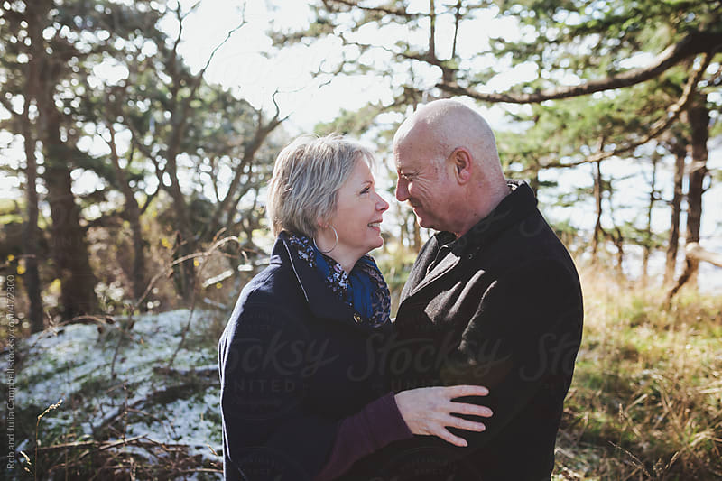 Happy older middle aged couple (fifties)  looking at each other smiling outside in winter by Rob and Julia Campbell for Stocksy United