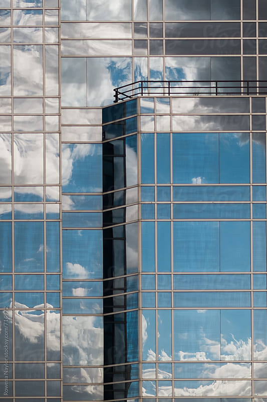 Reflection of blue sky and clouds on windows of building by Rowena Naylor for Stocksy United