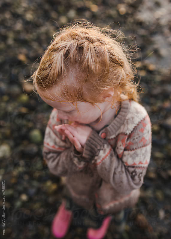 A little girl tries to warm her hands after getting wet and cold by Amanda Voelker for Stocksy United