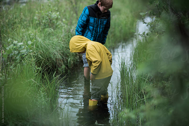 two boys on walk in a flooded path by Léa Jones for Stocksy United