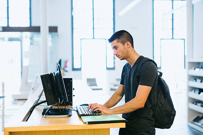 University man using internet in a computer lab. by BONNINSTUDIO for Stocksy United