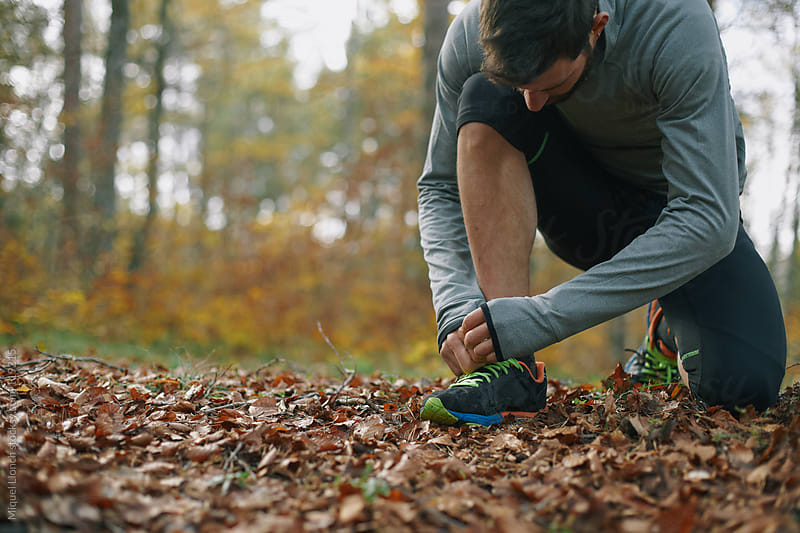 Runner tying his shoe outdoors  by Miquel Llonch for Stocksy United
