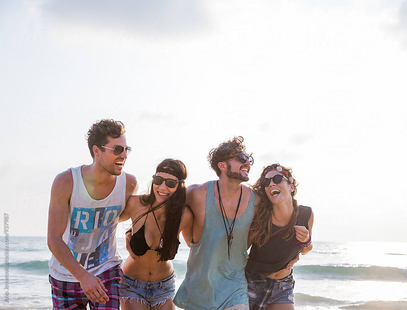 Shiny happy people - four friends laughing at the beach  by Jovo Jovanovic for Stocksy United