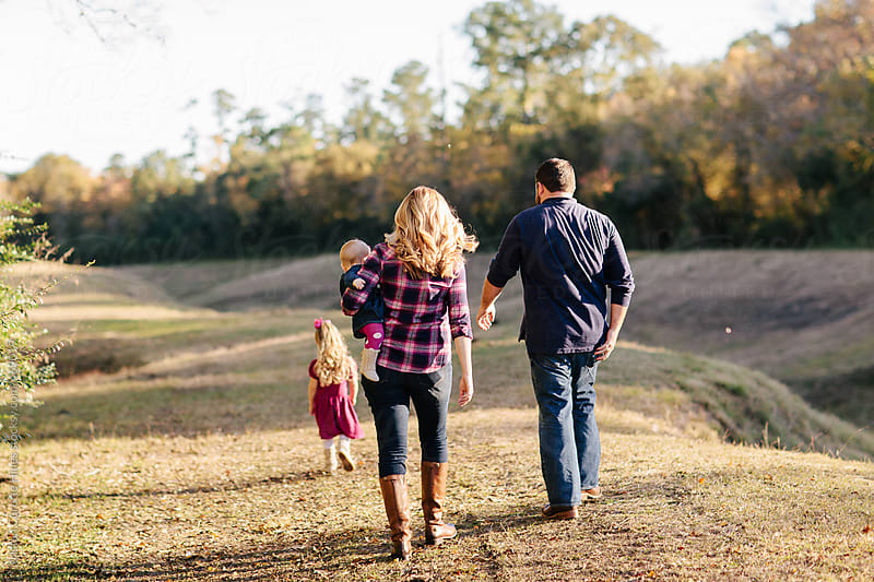 A beautiful family of four walking in the park together by Kristen Curette Hines for Stocksy United