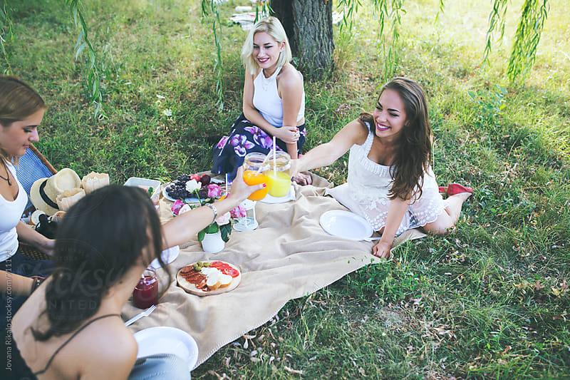 Female friends in the park having picnic by Jovana Rikalo for Stocksy United