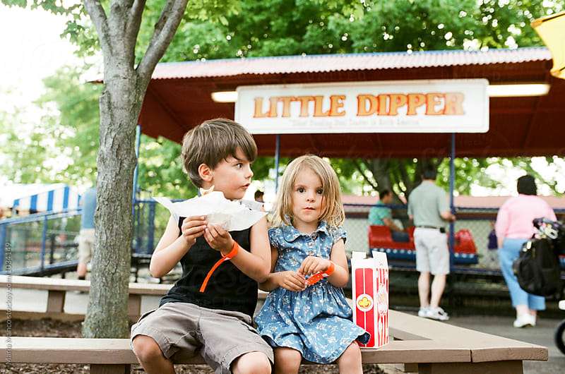 kids eating snacks at amusement park by Maria Manco for Stocksy United