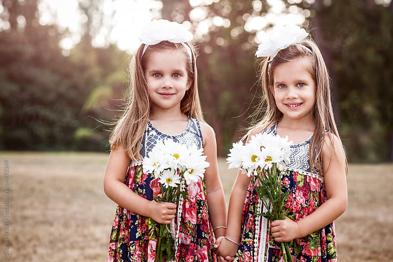 Portrait of twin sisters holding flowers in a park by Suprijono Suharjoto for Stocksy United
